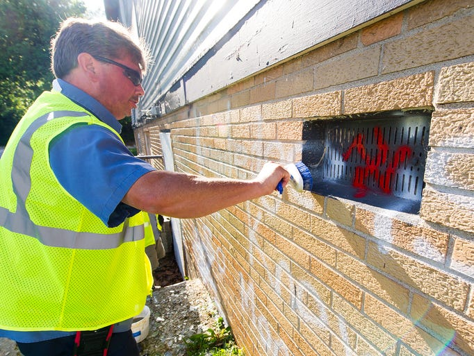 Robert Bowling, crew leader for DPW, scrubs away at graffiti on one of the many walls hit by vandals. Workers from the Indianapolis Department of Public Works used Elephant Snot and a pressure washer to remove graffiti that has polluted a vacant apartment complex on the south side of the city, Saturday, June 14, 2014.