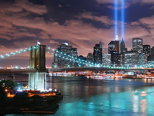 New York City's Manhattan panorama view with the Brooklyn Bridge and office building skyscrapers skyline illuminated over Hudson River in memory of September 11.