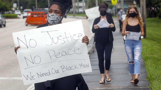 George Floyd protesters hold up signs just west of I-95 on Forest Hill Blvd., June 3, 2020.