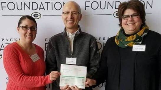 Erin Brown Stender, left, Scott Bader and Traci Bournoville receiving a Green Bay Packers Foundation grant.