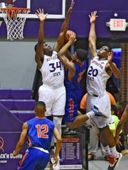 Louisiana College sophomore guard Lejawon LeBlanc (25) tries to muscle his way past NSU's Jordan Bell (34, left) and Ishmael Lane during Wednesday's game.