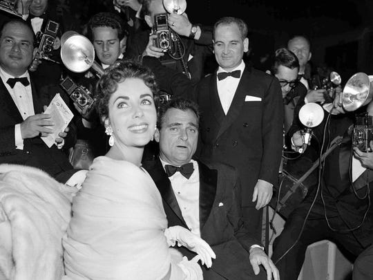 U.S. film star Elizabeth Taylor and her husband, producer Mike Todd are surrounded by photographers at the Cannes Film Festival at Cannes, France, May 2, 1955.