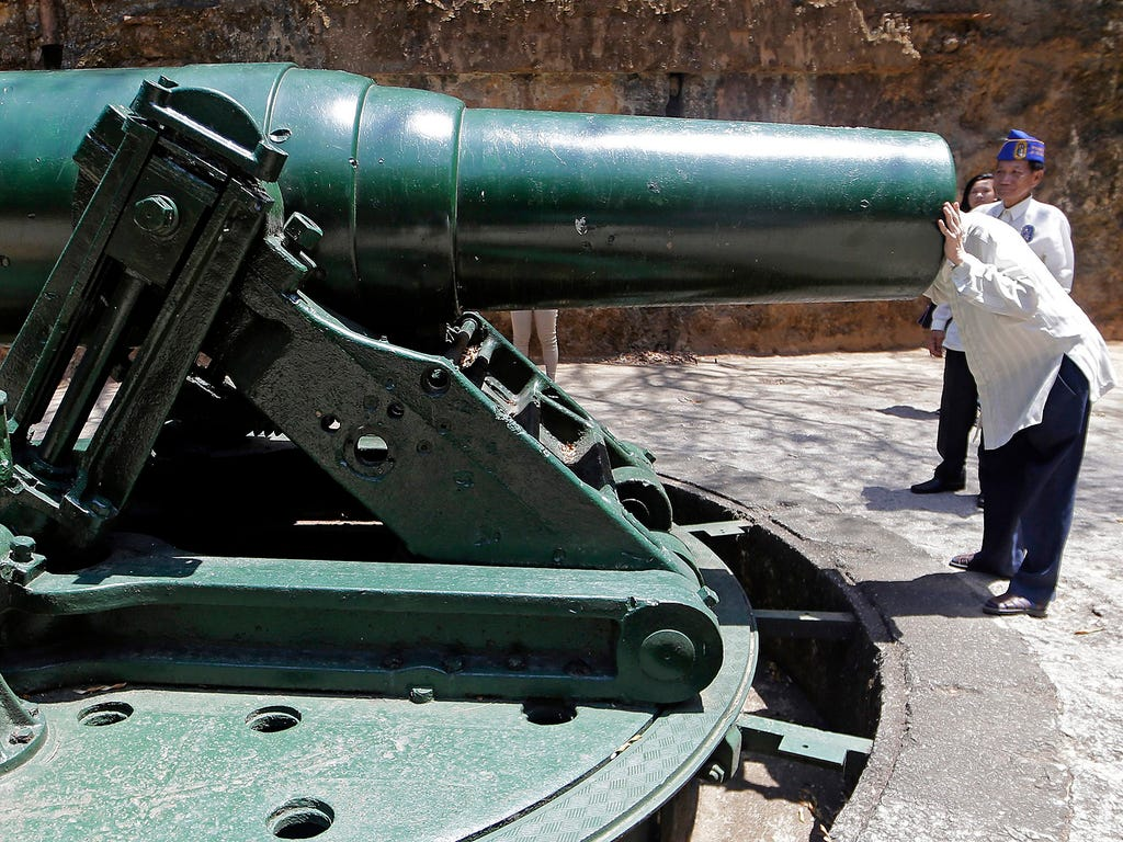 A World War II veteran peers into the barrel of a 12-inch coastal artillery mortar on April 7 on Corregidor Islandin the Philippines.