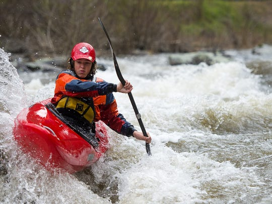 A kayaker navigates on a series of large rapids March