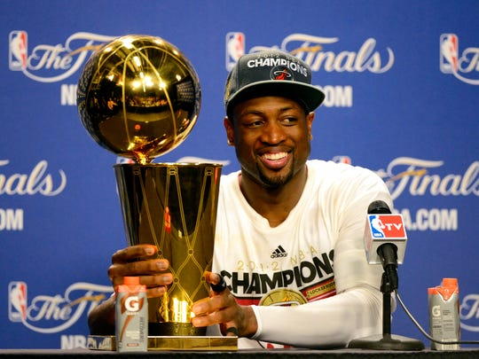 MIAMI, FL - JUNE 21:  Dwyane Wade #3 of the Miami Heat smiles next to the Larry O'Brien Finals Championship trophy after they won 121-106 against the Oklahoma City Thunder in Game Five of the 2012 NBA Finals on June 21, 2012 at American Airlines Arena in Miami, Florida. NOTE TO USER: User expressly acknowledges and agrees that, by downloading and or using this photograph, User is consenting to the terms and conditions of the Getty Images License Agreement.  (Photo by Ronald Martinez/Getty Images)