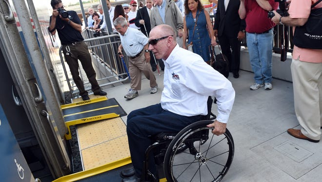 Billy Altom, of Little Rock prepares to board a waiting train using a newly designed bridge plate that bridges the gap between the platform and the train during an event to celebrate the 25th Anniversary of the Americans with Disabilities Act at the Amtrak station in Ann Arbor, Mich., on  July 23, 2015.