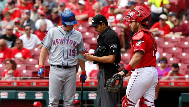 New York Mets right fielder Jay Bruce (19) looks over the lineup card with home plate umpire Gabe Morales (middle) during the first inning at Great American Ball Park. Reds catcher Tony Cruz looks on at right.