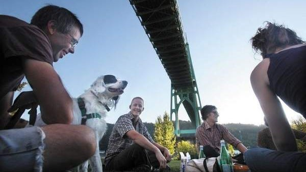 Ken Yates and his spaniel mix, Charlie, join a picnic, drinking San Pellegrino and eating ice cream sandwiches at Cathedral Park. The Portland park gets its name from the Gothic arches of the St. Johns Bridge overhead.