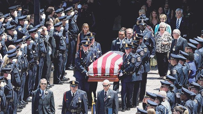 Police officers and family members escort the casket of slain IMPD officer Perry Renn out of Bankers Life Fieldhouse after his funeral on Friday, July 11, 2014.