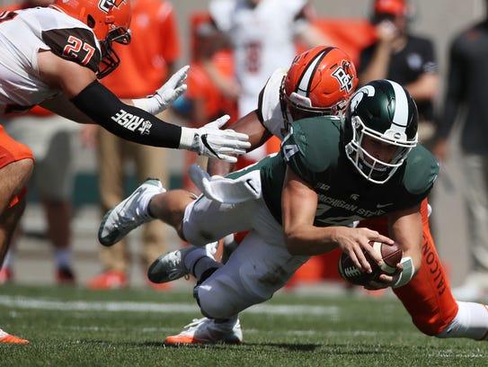 Michigan State quarterback Brian Lewerke dives for