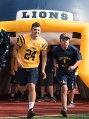 South Lyon player Will Kelley goes through the Lions' den with a Victory Day participant.