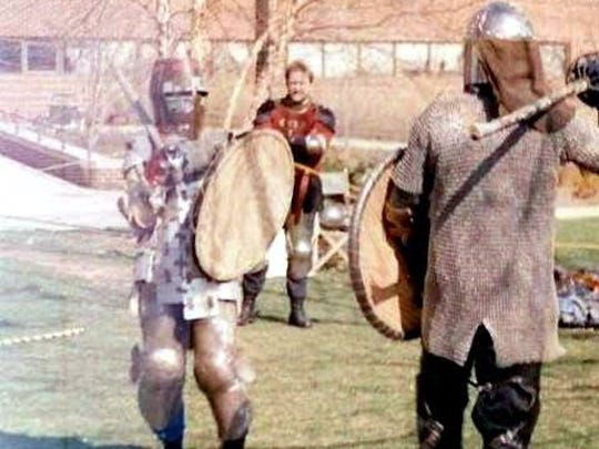 An older photo of Karen Dolley participating in unchoreographed fighting with rattan swords and wooden shields.