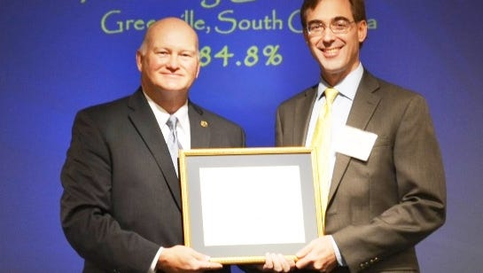 David White, (right) of Fostering Great Ideas, receives his Angel plaque from S.C Secretary of State Mark Hammond.