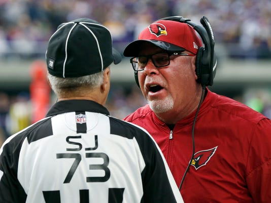 Arizona Cardinals head coach Bruce Arians, right, argues a call with side judge Joe Larrew during the first half of an NFL football game against the Minnesota Vikings Sunday, Nov. 20, 2016, in Minneapolis. Arians was in the hospital Monday after feeling ill overnight, the team said. The Cardinals issued a statement that said Arians was experiencing discomfort and not feeling well Sunday night after returning home from Arizona's game in Minnesota and his wife took him to the hospital. All tests conducted so far had come back favorably, the team said. (AP Photo/Jim Mone)