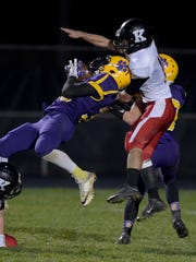 Hagerstown's Jalen Oliver grabs the ball against Knightstown's Steven Heady during a football sectional game Friday, Oct. 28, 2016 in Hagerstown.