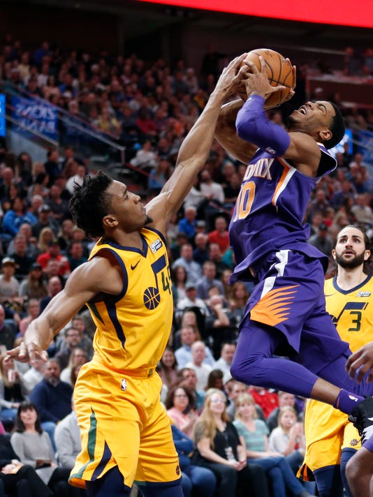 Utah Jazz guard Donovan Mitchell, left, blocks the shot of Phoenix Suns guard Shaquille Harrison (10) during the second half of an NBA basketball game Thursday, March 15, 2018, in Salt Lake City. (AP Photo/Rick Bowmer)