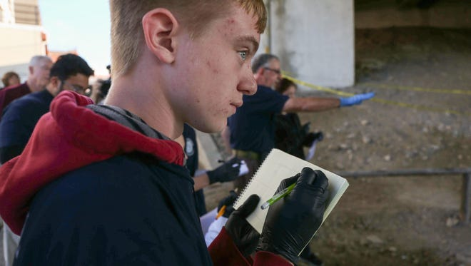 Andrew Trimble, a senior from Lincoln High School and a member of the Central Campus criminal justice program, takes notes at the scene of a mock homicide on Thursday, Oct. 8, 2015, outside of Central Campus in Des Moines.