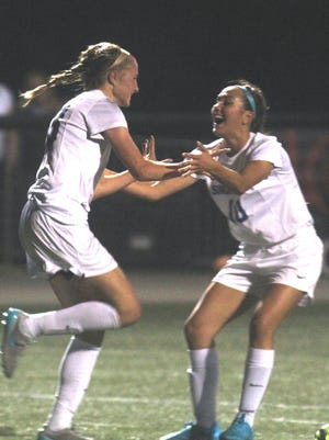 Gill Morris, right, congratulates Abigail Zoeller after Zoeller scored a goal late in the first half against Oldham County in the 8th Region girls soccer championship game Oct. 22, 2015.
