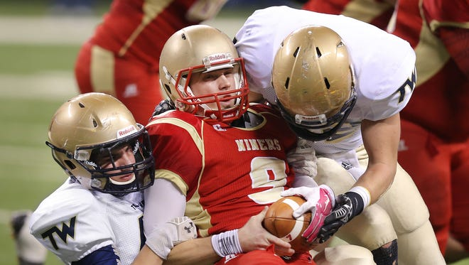 Andrean quarterback Jake Paliga is sacked by Tri-West players Cameron Cole, left, and Drake Stahl in the first half of the IHSAA 3A State Football Finals held at Lucas Oil Stadium on Saturday, Nov. 29, 2014.