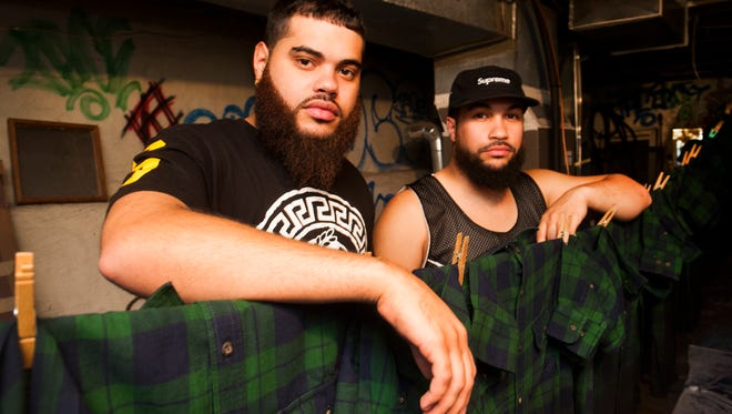 Brothers Jeffrey, 23, (left) and Luis Reyes, 24, of Sweettooth Specialtees pose for a portrait on a clothes line of freshly dyed shirts for their upcoming fall line, Sept. 20, 2013 in Camden, N.J.