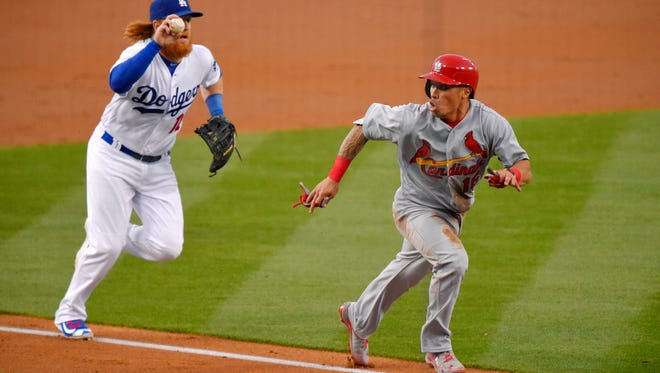 St. Louis Cardinals' Kolten Wong, right, is caught between third and home as Los Angeles Dodgers third baseman Justin Turner pursues during the second inning of a baseball game, Friday, May 13, 2016, in Los Angeles. Wong was tagged out by catcher A.J. Ellis on the play.