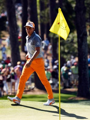 Rickie Fowler walks to the 7th green during the final round of The Masters golf tournament at Augusta National Golf Club.