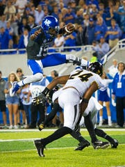 Kentucky quarterback Stephen Johnson leaps over Missouri safety Thomas Wilson during the second half of an NCAA college football game Saturday, Oct. 7, 2017, in Lexington, Ky. Kentucky won, 40-34.