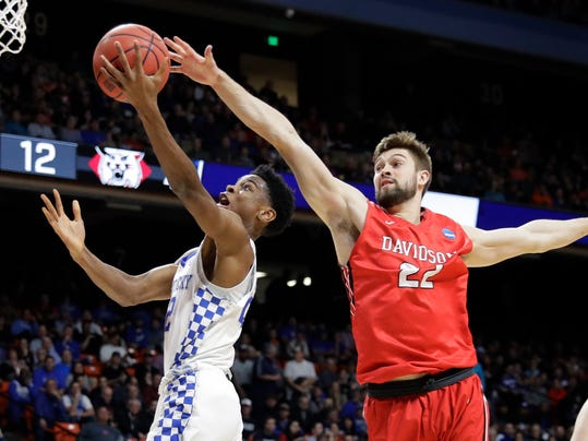 Kentucky guard Shai Gilgeous-Alexander, left, shoots as Davidson forward Will Magarity (22) defends during the first half of a first-round game in the NCAA men's college basketball tournament Thursday, March 15, 2018, in Boise, Idaho. (AP Photo/Otto Kitsinger)