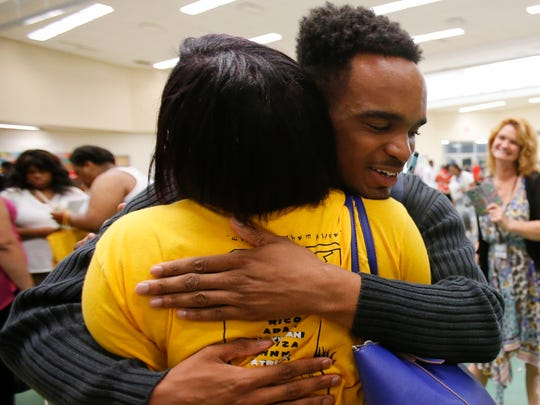 Taft High School graduating senior Taj Hogan, 18, right, gives English teacher Sinita Scott a hug after receiving his graduation gift, Thursday, May 12, 2016, at Taft High School in the West End.