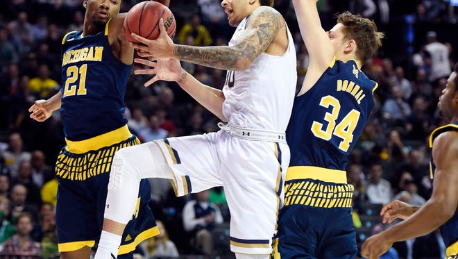 Notre Dame forward Zach Auguste (30) shoots against Michigan forward Mark Donnal (34) and guard Zak Irvin (21) in the first half of U-M's loss in the first round of the NCAA tournament Friday Brooklyn, N.Y.