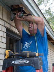 Scott Dunbar, a contractor for Rebuild Northwest Florida, works to retrofit a home by adding truss ties and closing off the soffit in June 2017.