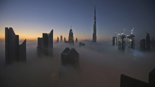 In this Dec. 31, 2016 file photo, the sun rises over the city skyline with the Burj Khalifa, the world's tallest building, on a foggy day in Dubai, United Arab Emirates. Dubai is tapping the global financial market to potentially raise billions of dollars for the first time in years. That's according to a bond prospectus seen on Tuesday, Sept. 1, 2020, by The Associated Press. It reveals the deepening toll of the coronavirus pandemic on Dubai's economy.