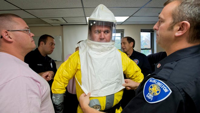 Burlington firefighters help fellow firefighter Nick Muzzy don a hazmat suit and respirator during routine hazardous materials response training at Station 2 on North Avenue in Burlington on Wednesday. First responders would don similar gear to respond to an Ebola-related call.
