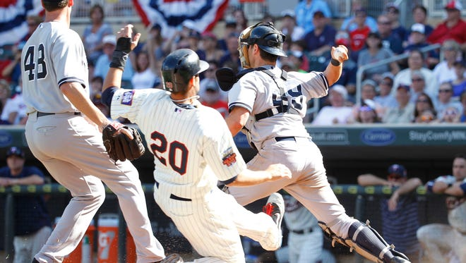 Yankees catcher Francisco Cervelli turns to throw to first base after forcing out the Twins' Chris Colabello  at home in the 11th inning of Saturday's game in Minneapolis. Cervelli made an error on the throw, allowing the Twins to score the winning run.