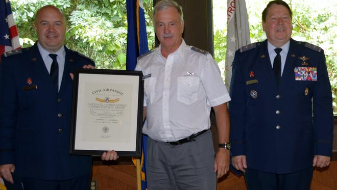 Colonel Francis Smith, Commander, South Carolina Wing, Civil Air Patrol, at left, and Colonel John Knowles, Commander, Middle East Region, Civil Air Patrol, at right, present Major Steven Askew with the National Commander's Commendation Award, at center.