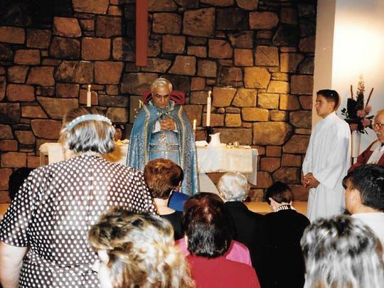 The Rev. Diran Papazian provides Holy communion to Lansing-area Armenians at the mission parish at St. David's Episcopal Church in Delta Township.
