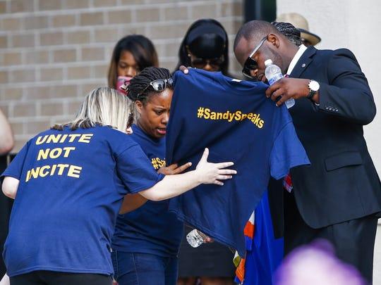 People look at a shirt with words '#SandySpeaks' printed