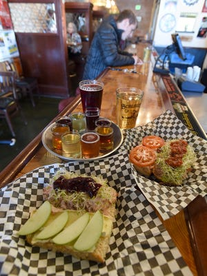 A Normandy sandwich, front, and a Wild Turkey sandwich are pictured with a flight of cider, a pint of Tart Cherry cider, and Della's Apple Struedel at Scrumpy's.