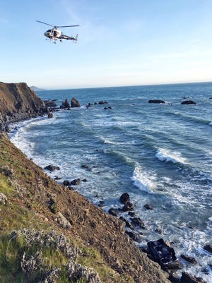 A helicopter hovers over steep coastal cliffs Tuesday, March 27, 2018, near Mendocino, Calif., where a vehicle, visible at lower right, plunged about 100 feet off a cliff along Highway 1, killing all five passengers.