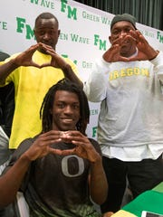 Fort Myers High school's Darrian Felix makes the University of Oregon sign alongside his father James Felix, right and older brother James Jr. as they celebrate National Signing Day Wednesday afternoon.