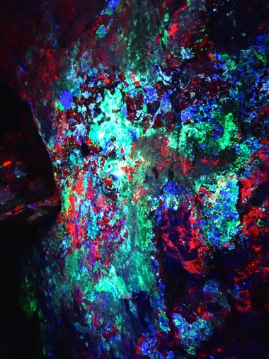 The fluorescent wall of the Hull Mine blazes to life