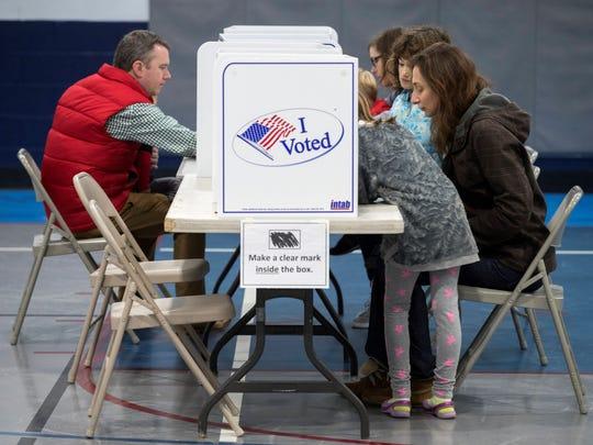 Votantes rellenan sus papeletas antes de ejercer su