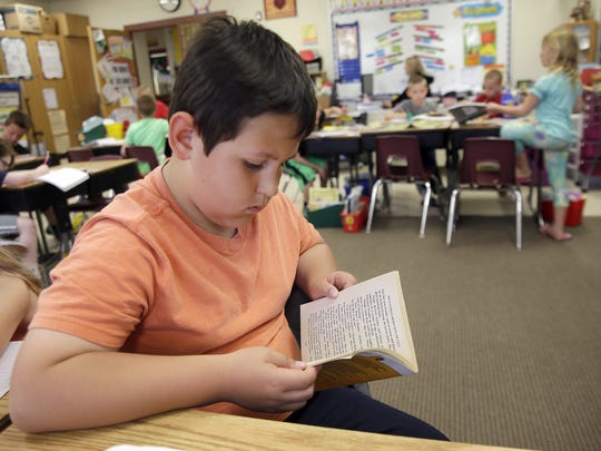 Second-grader Ayden Delgado reads a book in Tammy Charlier's classroom at Red Smith School.