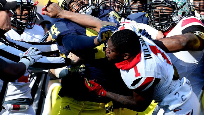 Michigan's Delano Hill is punched by Ohio State's Dontre Wilson during the second quarter Nov. 30, 2013 in Ann Arbor.