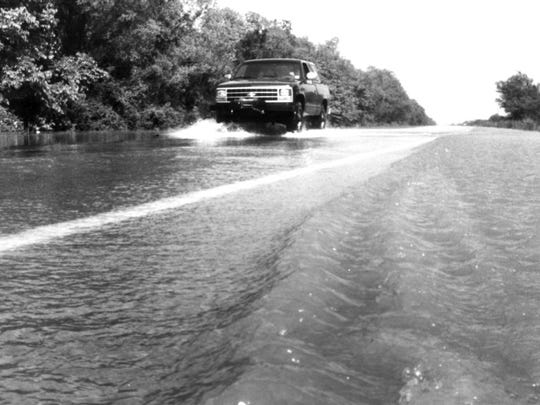 Water cascaded across Louisiana 15 near Bayou LaFourche. Pickup trucks continued to pass through in May 1991 though the road was officially closed.