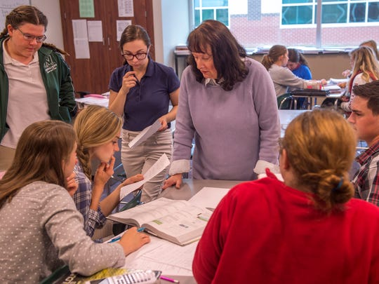 After splitting her North High School pre-calculus class into small groups, Jane Bernhardt, center, moves from group to group to answer any questions they may have on their homework Thursday this past school year.