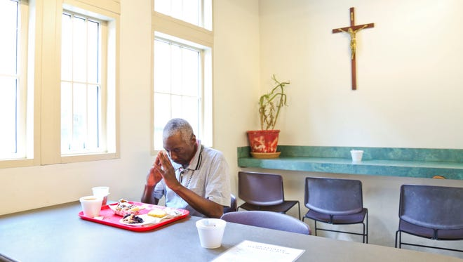 Luther Mason, 54, prays before eating a lunch of soup and bread, barbecue sandwich with pie free provided daily by the Cathedral of the Assumption. The city of Louisville plans to recognize the free meals of bologna and barbecue sandwiches with a marker at Cathedral Alley, known as Bologna Alley after bologna sandwiches were served from the same place during the 1930s and 1940s. Around 140 homeless and low-income people are served each day.