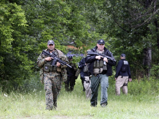 Law enforcement officers search a residential area for prison escapees David Sweat and Richard Matt on Monday in Saranac, N.Y. Law enforcement are in the 10th day of searching for the two killers who used power tools to cut their way out of Clinton Correctional Facility in Dannemora.