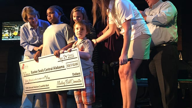 Autism Mudbug Ball organizers present a donation to Easter Seals of Central Alabama and some of the families who have benefited from its services.