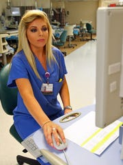 Patient care technician Tiffany Caranci works on a computer in the pre-operation and recovery department at Eisenhower Medical Center in Rancho Mirage, Calif. on Sunday, September 28, 2014. Caranci graduated in June with a nursing degree from the Palm Desert campus of California State University, San Bernardino.